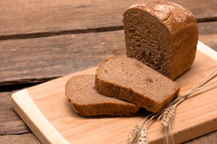 Fresh bread. Rustic bread and wheat on an old vintage planked wood table Stock Photography