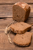 Fresh bread. Rustic bread and wheat on an old vintage planked wood table Stock Photos