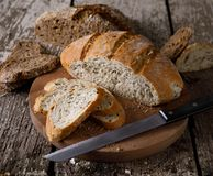 Fresh bread slice and cutting knife on rustic table. Royalty Free Stock Photos
