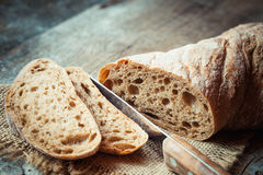 Fresh bread slice and cutting knife on  table Royalty Free Stock Photo