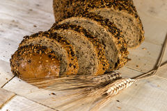 Fresh bread slice with sunflower seeds on wooden table Royalty Free Stock Photos