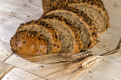 Fresh bread slice with sunflower seeds on wooden table Stock Images