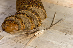Fresh bread slice with sunflower seeds on wooden table Stock Photos