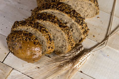 Fresh bread slice with sunflower seeds on wooden table Stock Photo