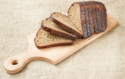 Fresh bread slice on wooden cutting board  burlap background Royalty Free Stock Photo