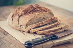 Fresh bread in slices on wooden cutting board, outdoors. Fresh dark bread in slices. Wooden cutting board and table, knife sliced food drink breakfast bakery rye royalty free stock images