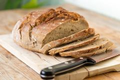 Fresh bread in slices on wooden cutting board, outdoors. Fresh dark bread in slices. Wooden cutting board and table, knife sliced food drink breakfast bakery rye royalty free stock image