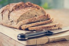 Fresh bread in slices on wooden cutting board, outdoors. Fresh dark bread in slices. Wooden cutting board and table, knife sliced food drink breakfast bakery rye stock photo