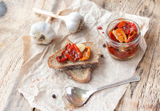 Fresh bread with sun-dried tomatoes on a wooden. Fresh bread with sun-dried tomatoes and garlic on a wooden table Royalty Free Stock Photos