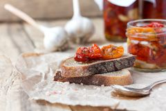 Fresh bread with sun-dried tomatoes on a wooden. Fresh bread with sun-dried tomatoes and garlic on a wooden table Royalty Free Stock Photography