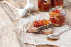 Fresh bread with sun-dried tomatoes on a wooden. Fresh bread with sun-dried tomatoes and garlic on a wooden table Stock Photo