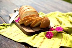 Fresh Bread On Table. Fresh Bread On Chopping Board With Knife And Flowers On An Old Wooden Table Royalty Free Stock Images
