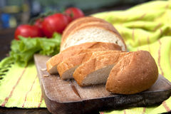Fresh Bread On Table. Fresh Bread On Chopping Board With Tomatoes And Salad In The Background Royalty Free Stock Photos