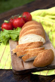 Fresh Bread On Table. Fresh Bread On Chopping Board With Tomatoes And Salad In The Background Stock Photos