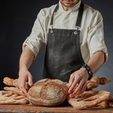 Fresh bread on the table. A variety of fresh organic bread on a wooden brown table, baker keeps bread Royalty Free Stock Photo