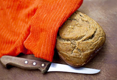 Fresh bread under a napkin and knife Royalty Free Stock Images