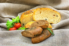 Fresh bread and vegetables  on textiles. Fresh bread and tomato, vegetables  on textiles Royalty Free Stock Photography