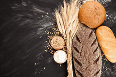 Fresh bread and wheat. On black background royalty free stock photography