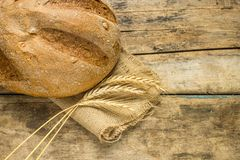 Fresh bread with wheat ears on wooden table. Stock Images