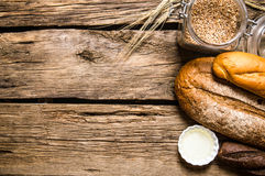 Fresh bread with wheat grains. On wooden table. Royalty Free Stock Photos