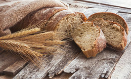 Fresh bread and wheat on the old wooden background. Toned Stock Image