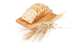 Fresh bread and wheat on white. Fresh bread on wooden plate and wheat on white royalty free stock photo