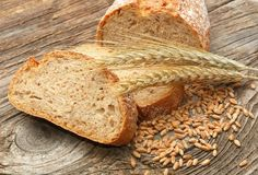 Fresh bread and wheat on wooden background Stock Image