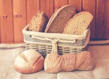 Fresh bread in wicker basket and near on table. Royalty Free Stock Photos