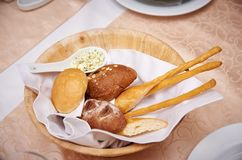 Fresh bread in a wooden bowl on a served table royalty free stock images