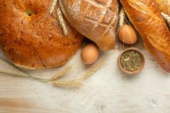 Fresh bread on a wooden table with flour and wheat, eggs and empty space. Concept baking, bakery royalty free stock image