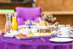 Fresh Breakfast or brunch with ham, eggs, bread, yogurt, fruits. And coffee on violet table and white dishware Stock Photo