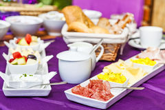 Fresh Breakfast or brunch with ham, eggs, bread, yogurt, fruits. And coffee on violet table and white dishware Stock Image