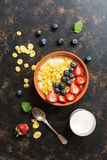 Fresh breakfast-corn flakes with milk, strawberries and blueberries on a dark background. View from above, flat lay. royalty free stock photos