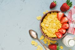 Fresh breakfast, cornflakes, milk and fresh strawberries on a gray concrete background. The concept of healthy eating. Top view, c. Opy space Stock Photos