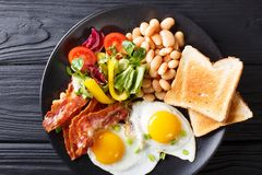 Fresh breakfast: fried eggs with bacon, beans, toast and vegetab