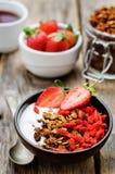 Fresh breakfast of granola, yogurt, nuts, goji berries and straw Royalty Free Stock Photo