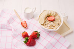 Fresh breakfast of healthy oatmeal with banana slices, strawberr Royalty Free Stock Images