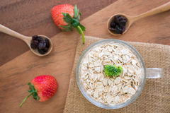 Fresh breakfast of healthy oatmeal in glass with strawberries on. Wooden background Royalty Free Stock Photography