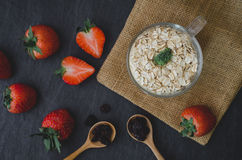 Fresh breakfast of healthy oatmeal in glass with strawberries on. Wooden background Royalty Free Stock Photos