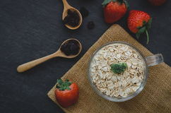 Fresh breakfast of healthy oatmeal in glass with strawberries on. Wooden background Royalty Free Stock Images