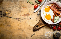 Fresh Breakfast plate. Fried eggs with bacon and tomatoes. Stock Images