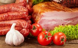 Fresh breakfast table with pork ham, sausage and vegetables. On wood with spices and salad stock images