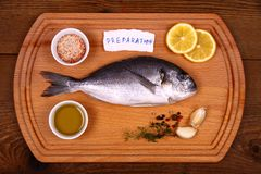 Fresh bream fish on cutting board with ingredients, pieces of paper Royalty Free Stock Image