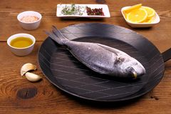 Fresh bream fish on frying pan with ingredients Royalty Free Stock Photos