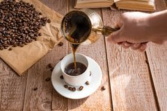 Free Fresh Breved Coffe In Cezve Traditional Turkish Coffee Pot Woman`s Hand Pours Coffee Into White Cup Royalty Free Stock Images - 154725429