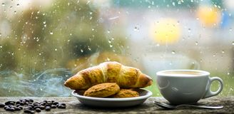 Fresh brewed coffee in white cup or mug on windowsill. Coffee drink with croissant dessert. Enjoying coffee on rainy day. Coffee time on rainy day. Wet glass stock image