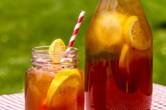 Fresh Brewed Ice Tea on the Patio. Close up of mason jar mug and tall pitcher filled with fresh brewed iced tea and lemon slices with red swirl straws sitting on Stock Photo