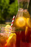 Fresh Brewed Ice Tea on the Patio. Close up of mason jar mug and tall pitcher filled with fresh brewed iced tea and lemon slices with red swirl straws sitting on Stock Image