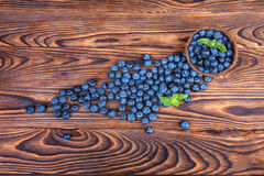 Fresh and bright blueberries. Healthy, ripe, raw and bright dark blue berries on a wooden background. Copy space. Summer fruits. Royalty Free Stock Photography