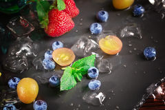 Fresh and bright blueberry, grapes and strawberry with mint and ice cubes. Healthy, juicy berries on a black background. Royalty Free Stock Images